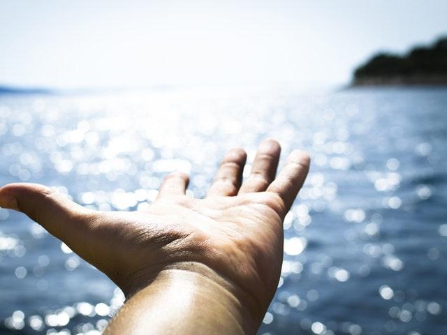 En hand och solbelyst hav